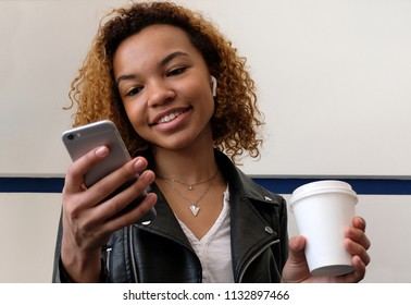 The girl holds a white glass in her hand, looks into the phone and smiles. A beautiful young modern black woman, in a leather jacket with airpods in her ear.