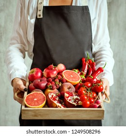 girl holds wooden tray with fresh red vegetables and fruits on grey background. Healthy eating vegetarian concept. Close up.