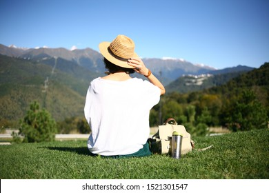The girl holds a woven straw hat on her head with her hand and looks at the mountain peaks with blue sky. Camping style. forest man sits with his back on the grass next to a mug and a backpack.