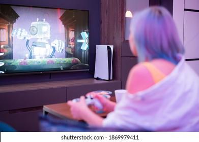 Girl at home playing PlayStation 5 gaming console at home. Moscow - November 28 2020.