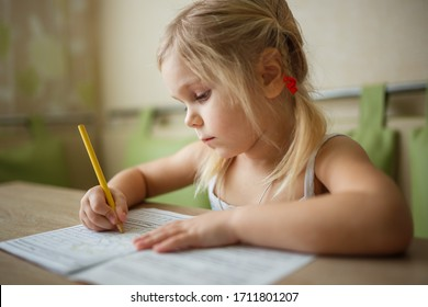 a girl at home writes draws, classes for a child at home
