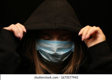 The girl in the hood. Black background. Girl in a medical mask. Crime.