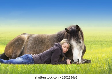 Girl and horse lying and sleep on field, sunny summer day,  against  blue sky