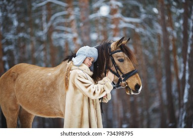 The girl with  horse in snowy forest in the winter walks in nature