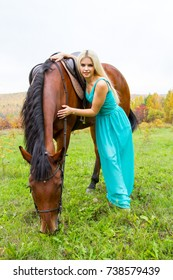 Girl with a horse walking in an autumn forest