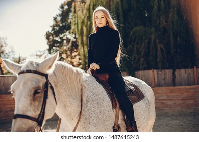Girl with a horse. Woman in a ranch. Blonde in a black sweater
