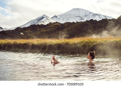 Girl in a hot spring in Iceland Landmannalaugar. Relaxing in a natural hot bath.