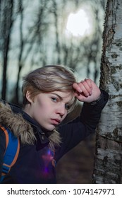 The girl huddled by the trunk of a birch
