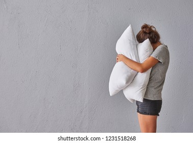 Girl hug pillow in front of the grey stone wall.