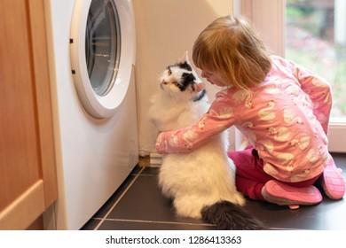 Girl hugging cat near washing machine in kitchen