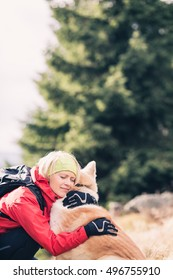 Girl Hugging Dog. Woman hiking with akita inu dog on forest trail. Recreation and healthy lifestyle outdoors, autumn woods in mountains, inspirational nature. Fitness, trekking and activity concept.