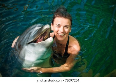 Girl hugging a dolphin in the water