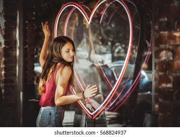 girl hugging heart in a shop window