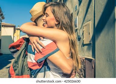 Girl is hugging her boyfriend just back from his trip - caucasian people - urban scene