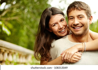 Girl hugging his boyfriend, both looking at the cam and smiling