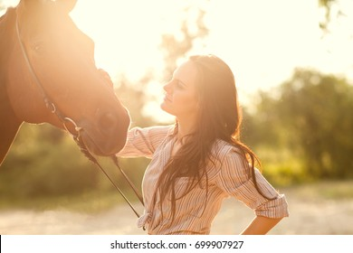 Girl hugging with a horse at sunset