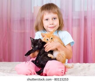 Girl hugging red and black kitten