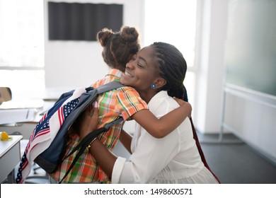Girl hugging teacher. Cute little schoolgirl hugging her pleasant teacher while feeling thankful