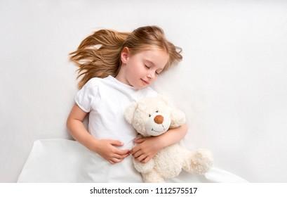 Girl hugging teddy bear laying on bed