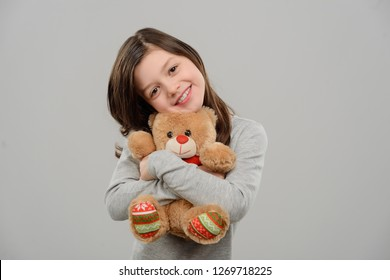 Girl hugging a Teddy bear. Sincere smile and strong embrace. Cute half-length portrait of a kid with toy.