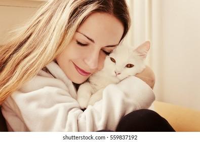 Girl hugging white cat