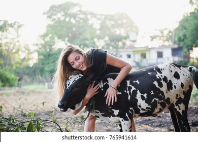the girl hugs the cow