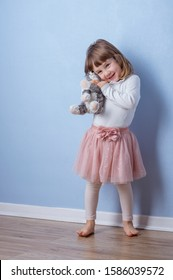 Girl hugs a fluffy cat toy staying on the floor. Clear blue background and copy space on the top.