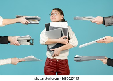 Girl hugs a large stack of documents and folders. At this time, employees are giving her a new job, loading the girl even harder