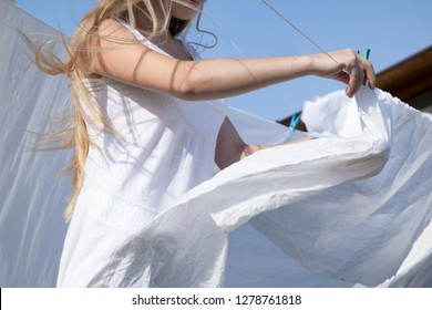 Girl hung up sheets on clothesline. On a sunny day outdoors. Strong wind blows the sheets