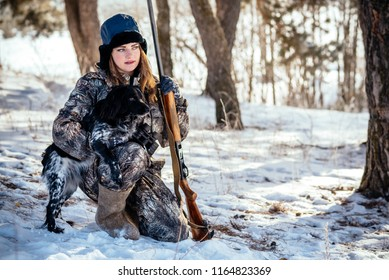 Girl hunter with binoculars in the forest, shows dog direction seeking mining. Concept of photo hunting with dogs, hounds.