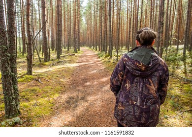 Girl in hunter camouflage walking in forest