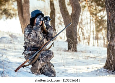 A girl hunter looks through binoculars in the woods, looks out for prey. The concept of modern hunting, equipment