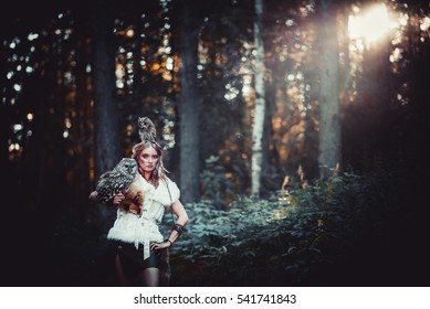 The girl is the huntress in the forest with owls in the hand and the head in the sun