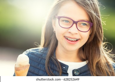 Girl with ice cream glasses and  dental braces. Portrait of a smiling young teenager.