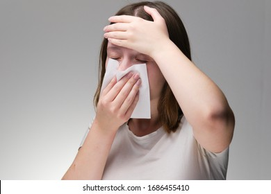 the girl is ill and blows her nose in a napkin