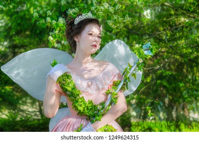 A girl in the image of a fairy queen with magic wand in a garden under a flowering tree on a summer sunny day.