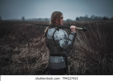 Girl in image of Joan of Arc (Jeanne d'Arc) in armor and with sword in her hands stands on meadow in middle of dry grass. Back view.