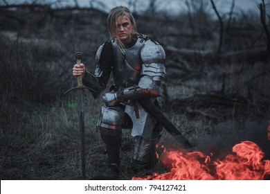 Girl in image of Joan of Arc (Jeanne d'Arc) in armor and with sword in her hands kneels on meadow against background of fire, black smoke and dry grass.