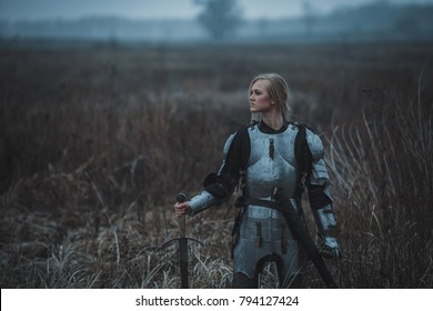 Girl in image of Joan of Arc (Jeanne d'Arc) in armor and with sword in her hands stands on meadow in middle of dry grass. Closeup.