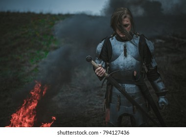 Girl in image of Joan of Arc (Jeanne d'Arc) in armor and with sword in her hands stands on meadow against background of fire, black smoke and grass.