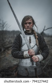 Girl in image of Joan of Arc (Jeanne d'Arc) with wounds on her face stands on meadow in armor and with sword in her hands.