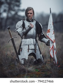 Girl in image of Joan of Arc (Jeanne d'Arc) in armor kneels with flag in her hands and sword on meadow against background of dry grass.