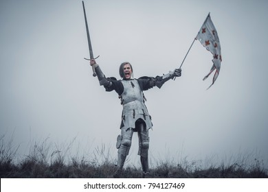 Girl in image of Joan of Arc (Jeanne d'Arc) stands in armor and issues battle cry with sword raised up and flag in her hands against background of sky and dry grass.