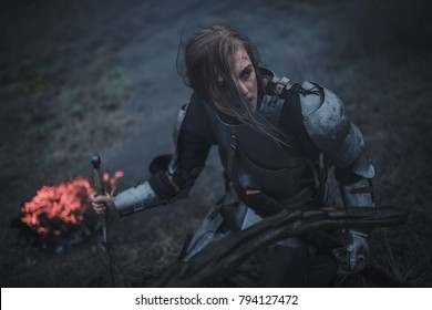 Girl in image of Joan of Arc (Jeanne d'Arc) in armor and with sword in her hands kneels against background of fire and black smoke. Closeup.