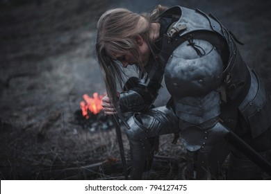 Girl in image of Joan of Arc (Jeanne d'Arc) kneels in armor and with sword in her hands against background of fire, smoke and dry grass. Closeup.
