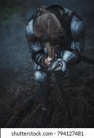 Girl in image of Joan of Arc (Jeanne d'Arc) in armor and with sword in her hands kneels against background of dry grass. Closeup.