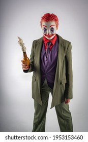 A girl in the image and makeup of a clown (white face, red clown mouth, blue diamonds on her eyes, green suit and red shirt) holds a Molotov cocktail in her hands. An anarchist clown, sinister. Joker