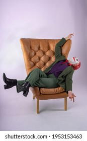 The girl in the image and make-up of a clown (white face, red clown mouth, blue diamonds on the eyes, green suit and red shirt) pretentiously lies on a brown leather vintage chair. The Sinister Clown