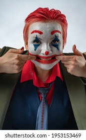 A girl in the image and makeup of a clown (white face, red clown mouth, blue diamonds on her eyes, green suit and red shirt) stretches a smile on her face with her fingers.Sad clown, sinister. Joker