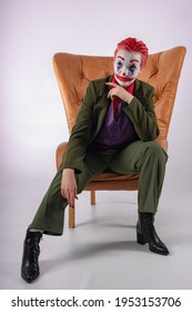 The girl in the image and makeup of a clown (white face, red clown mouth, blue diamonds on the eyes, green suit and red shirt) sits on a brown leather vintage chair. The Sinister Clown